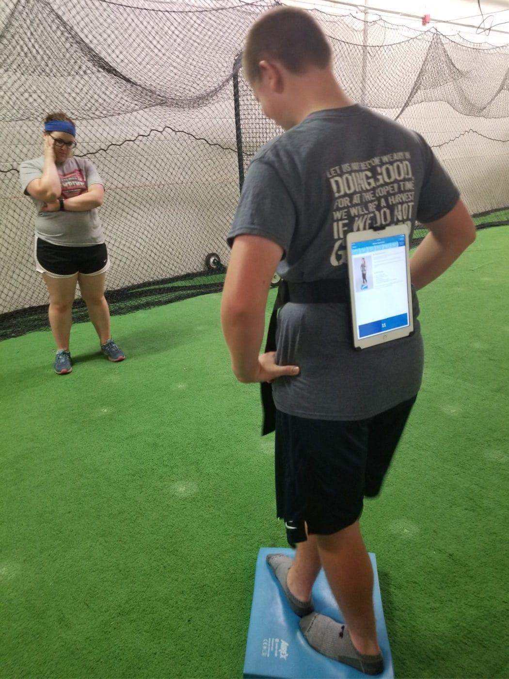 HaysMed Athletic Trainer Jensen Scheele administers a balance test.